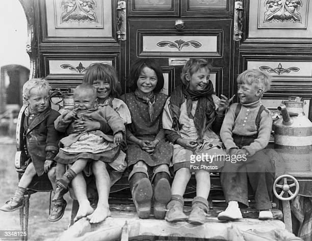 Gypsy children sitting on footplate of an ornate gypsy caravan