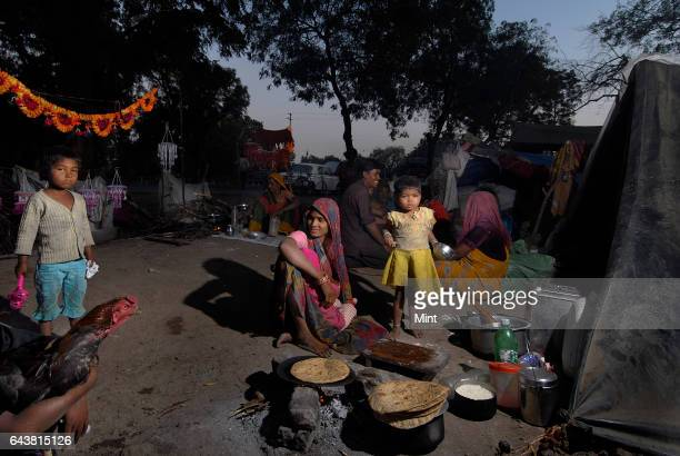 A gypsy family prepares dinner at their make shift roadside house in Dhule on Mumbai Agra Natioan Highway No 3 on January 21 2010 in Mumbai India