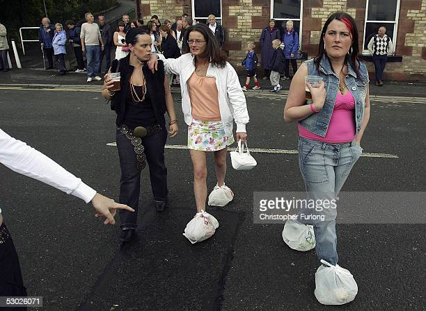 Gypsy girls wear plastic carrier bags on their feet to protect their best shoes from mud at Appleby Horse Fair on June 4 2005 in ApplebyinWestmorland...