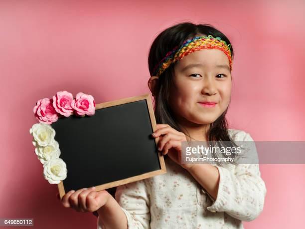 Gypsy hippie style cute girl, holding small blackboard