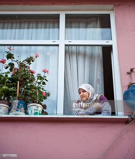 Gypsy looking out her window in Tarlabasi District Istanbul, Turkey