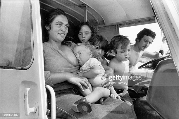 A gypsy mother and father sit inside a van with their four children the mother breastfeeding an infant