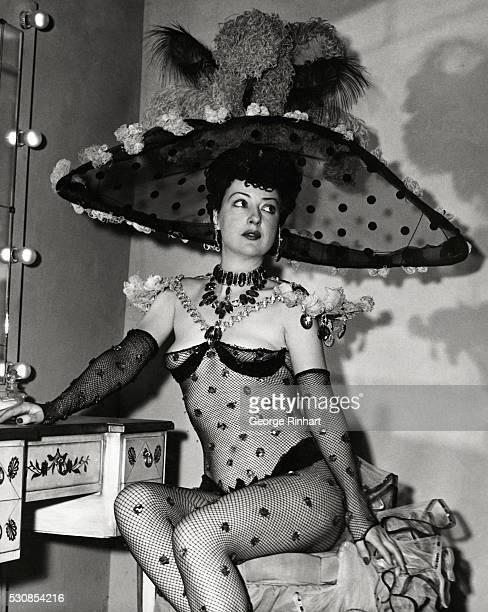 Gypsy Rose Lee, the famous burlesque queen and author, shown seated at the makeup table in her dressing room before a show. She is wearing a...