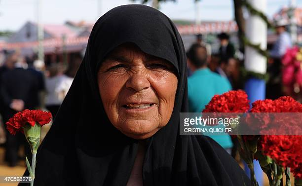A gypsy woman sells carnations during the Feria de Abril in Sevilla on April 21 2015 The fair dates back to 1847 when it was originally organized as...