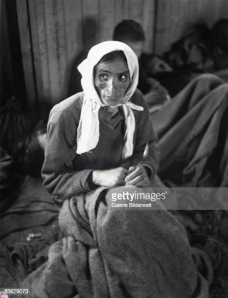 A gypsy woman suffering from typhus at BergenBelsen concentration camp waits with other gypsies for medical treatment April 1945 60000 civilian...