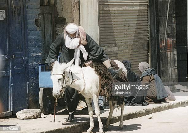 Wie in alten Zeiten besteigt ein Mann auf den Straßen Luxors seinen mit einem Schafsfell gesattelten Esel Hinter ihm sitzt ein Paar auf dem Gehweg...