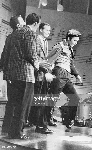 Gyrating Elvis Presley rocked 'n rolled as usual in his final appearance on Ed Sullivan's TV show tonight, but home viewers saw him only from the...
