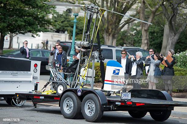 A gyrocopter emblazoned with a US Postal Service logo that was flown onto the West Front lawn of the Capitol is hauled away through the East Front...