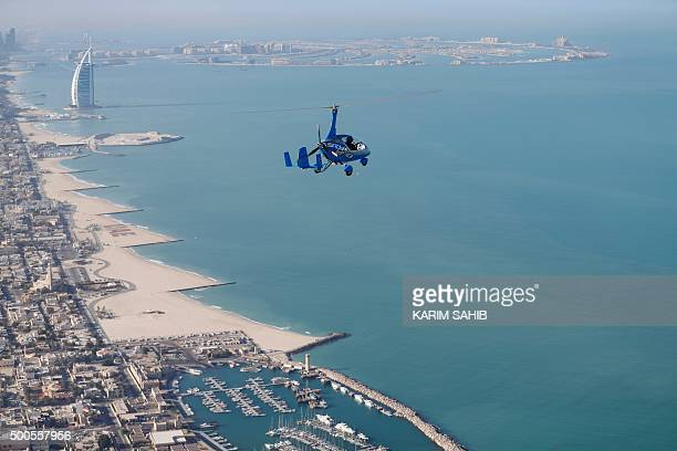 A gyrocopter flies over the capital of the United Arab Emirates Dubai during the World Air Games 2015 on December 9 2015 / AFP / KARIM SAHIB