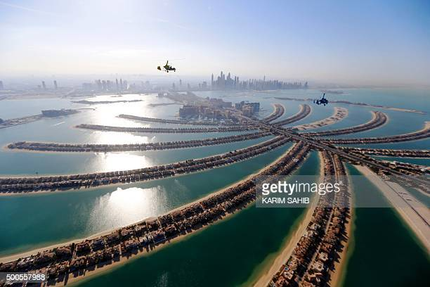 TOPSHOT Gyrocopters fly over the capital of the United Arab Emirates Dubai during the World Air Games 2015 on December 9 2015 AFP PHOTO / KARIM SAHIB...