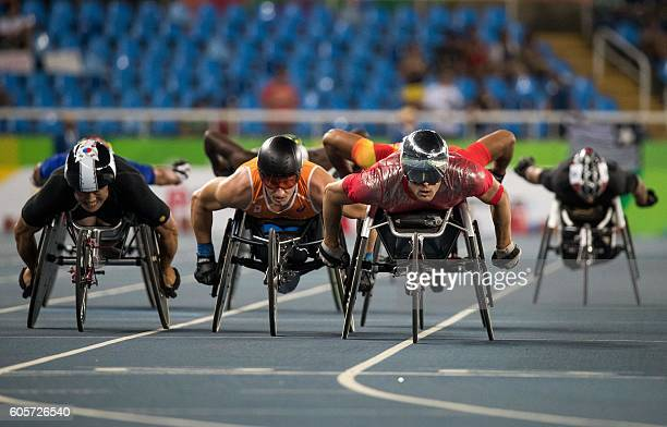 Gyu Dae Kim of Korea Kenny van Weeghel of the Netherlands and Marcel Hug of Switzerland lead in heat 2 of the wheelchair racing men's 800m T54 at the...