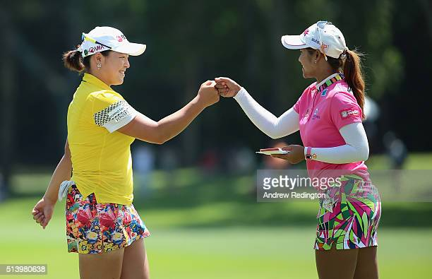 Ha Na Jang of South Korea and Pornanong Phatlum of Thailand bump knuckles on the 16th hole during the final round of the HSBC Women's Champions at...