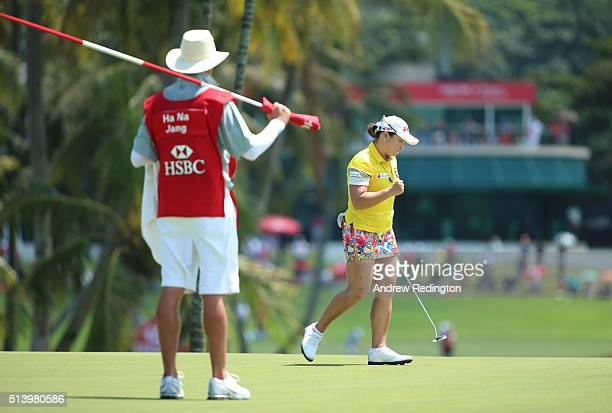 Ha Na Jang of South Korea celebrates holing a par putt on the 16th hole as her caddie Graeme Courts looks on during the final round of the HSBC...