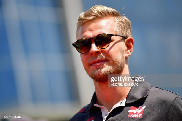 Haas F1's Danish driver Kevin Magnussen walks down the paddock prior to the race of the Formula One Hungarian Grand Prix at the Hungaroring circuit...