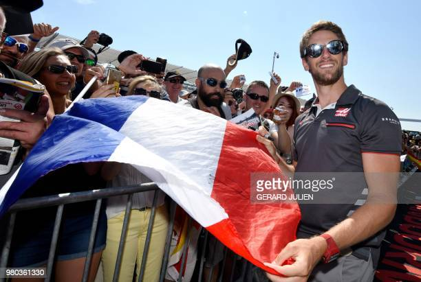 Haas F1's French driver Romain Grosjean poses with a French flag and fans at the Circuit Paul Ricard in Le Castellet, southern France, on June 21 a...