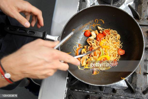 Haas F1's French driver Romain Grosjean prepares a pasta dish during his free time at the Hermanos Rodriguez racetrack in Mexico City on October 25...