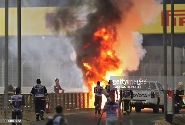 Haas F1's French driver Romain Grosjean's car burns after crashing during the Bahrain Formula One Grand Prix at the Bahrain International Circuit in...