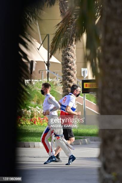 Haas F1's German driver Mick Schumacher crosses paths witha team member during the third practice session ahead of the Bahrain Formula One Grand Prix...