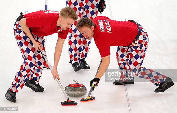 Haavard Vad Petersson and Torger Nergaard of Norway sweep a path for the stone during the men's curling round robin game between Canada and Norway on...