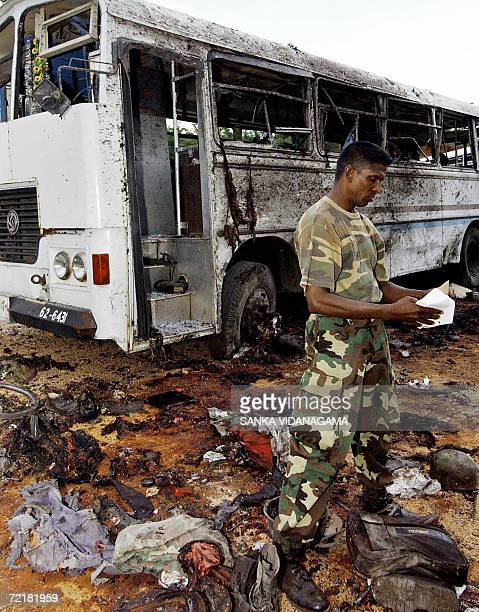 A Sri Lankan security personnel looks at the remains of a truck used by Tamil Tiger rebels to stage a suicide attack against bus loads of navy...