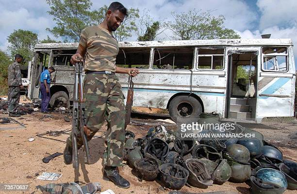 In this picture taken 17 October 2006, Sri Lankan sailors remove bloodied military equipment from the wreckage of buses in Habarana, after the...