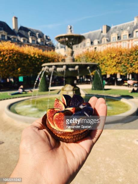 Habd holding tartelette with fresh fig personal perspective view, Paris, France