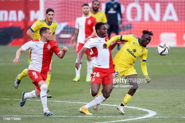 Habeeb Omobolaji 'Boddy' Adekanye of Cadiz CF battles for the ball with Sebastian Carlos Cristoforo and Ibrahima Kebe of Girona FC during the Copa...