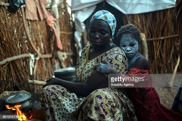 Habiba Alyu a Nigerian woman living in Malkoli camp in the Yola city of Adamawa is seen near her daughter Ayse on May 14 2015 Nigerian families who...