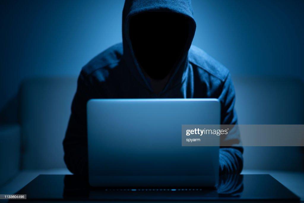 Hacker dark face using laptop : Stock Photo