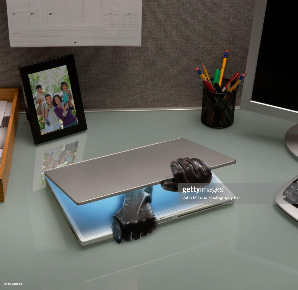 Hacker gloves opening laptop on office desk : Stock Photo