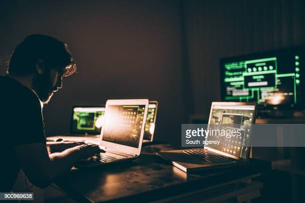 hacker in dark room - fraud stock pictures, royalty-free photos & images