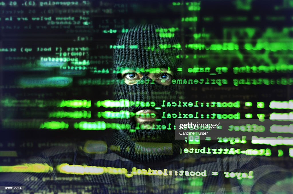Hacker looking at computer screen : Stock Photo