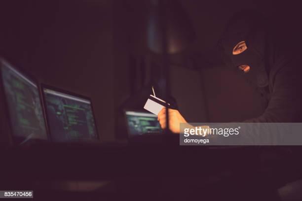 クレジット カードおよび夜のラップトップに取り組んでの情報を盗むハッカー