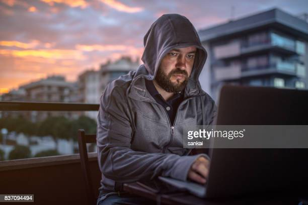 Hacker uses laptop in the night