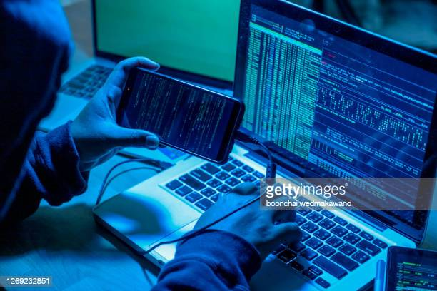 hacker with computers in dark room. cyber crime - computer hacker stock pictures, royalty-free photos & images