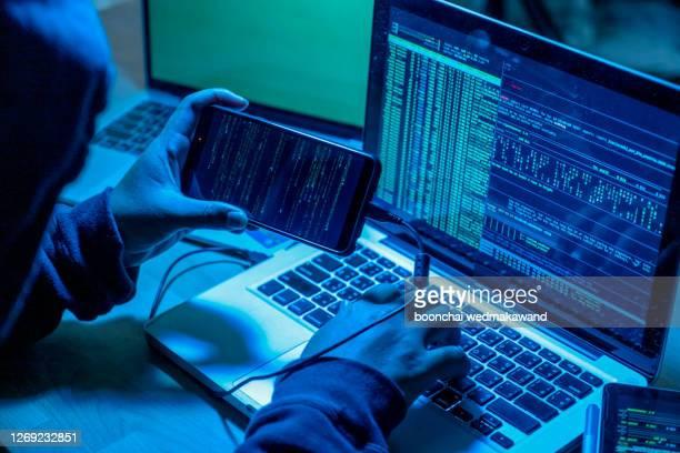 hacker with computers in dark room. cyber crime - criminalità informatica foto e immagini stock