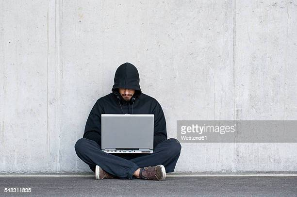hacker with laptop sitting in front of concrete wall - hacker imagens e fotografias de stock