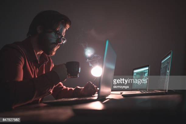 Hacker working on laptop and stealing informations