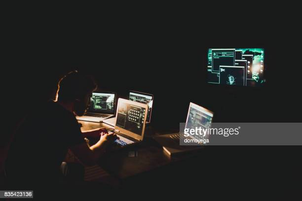 hacker working on laptop late at night - criminal investigation stock pictures, royalty-free photos & images