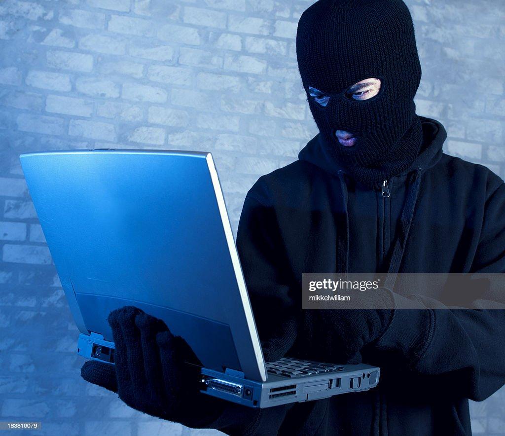 Hacker works on laptop at night : Stock Photo