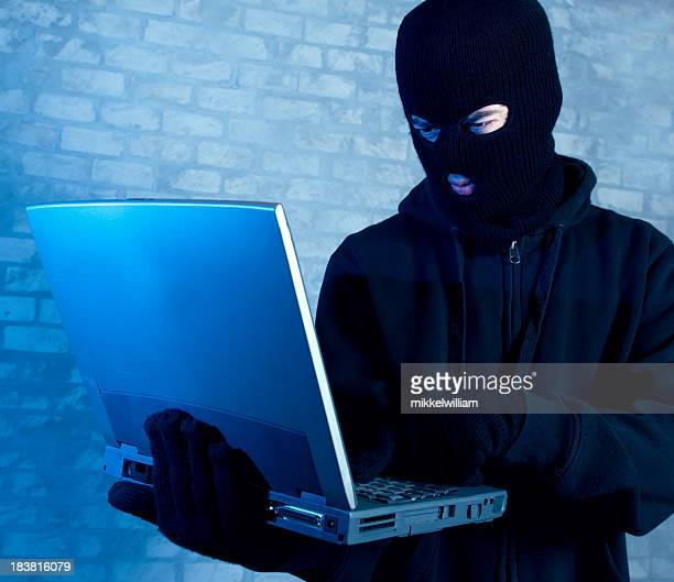 Hacker works on laptop at night