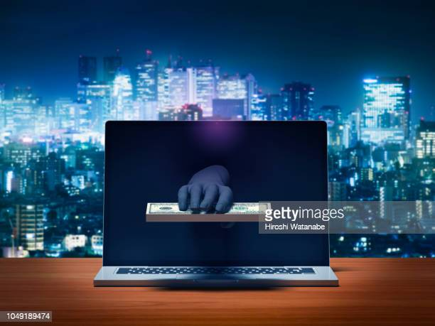 hacker's hand stealing money from laptop computer monitor - computer virus stock pictures, royalty-free photos & images