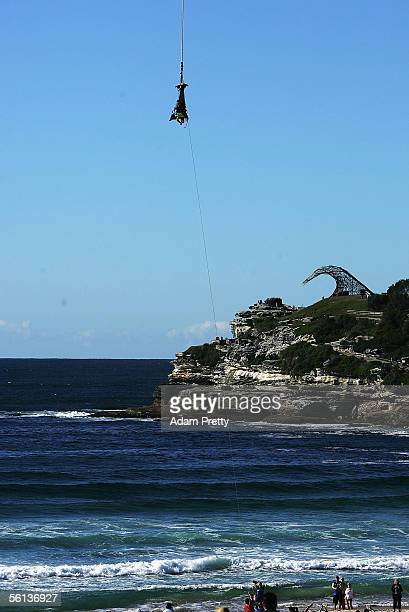 Hackett and Grant Denyer are lowered to the sand after bungy jumping out of a helicopter at Bondi Beach November 11 2005 in Sydney Australia The pair...