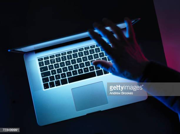 hacking, man opening laptop computer - data privacy stock pictures, royalty-free photos & images