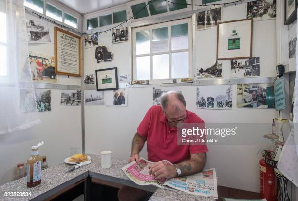 Hackney Carriage taxi driver reads the agony aunt section of a newspaper as he waits for his full English cooked breakfast inside the Warwick Avenue...