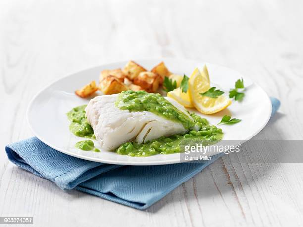 Haddock fillet with fried potatoes, minted pea sauce and lemon wedges