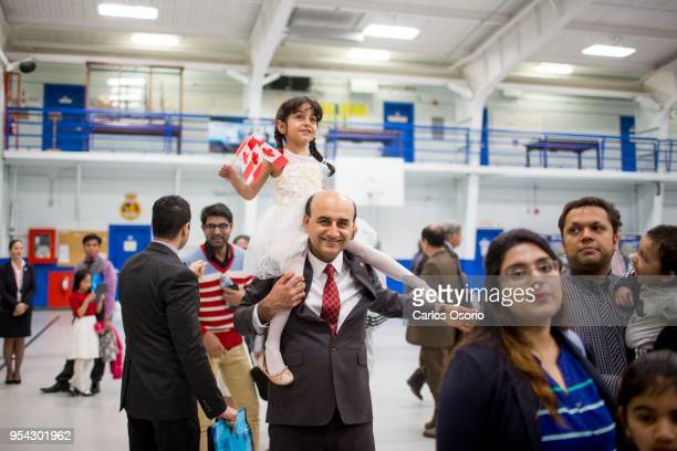 Hadi Elhami, originally from Iran, carries his daughter, Arnika Elhami, on his shoulder during a citizenship ceremony held at the Royal Canadian Navy...