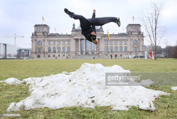 Hadi from Denmark jumps over one of the last heaps of snow during a stop of his tourist group in front of the Reichstag Building in Berlin Germany 28...