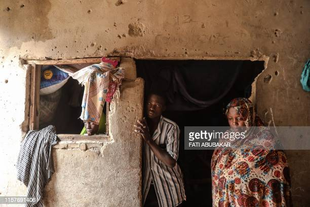 Hadiza, an internally displaced person from Baga local government area in Borno State in Nigeria, poses with family members on July 21, 2019 in...