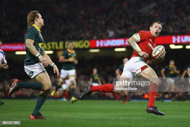 Hadleigh Parkes of Wales looks back towards Andries Coetzee of South Africa as he scores his sides third try during the International match between...